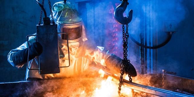 Strokovnjak, v temnem prostoru v zaščitni obleki, pri delu v težki industriji, se sklanja nad ognjem in upravlja z jeklenimi verigami in elementi.