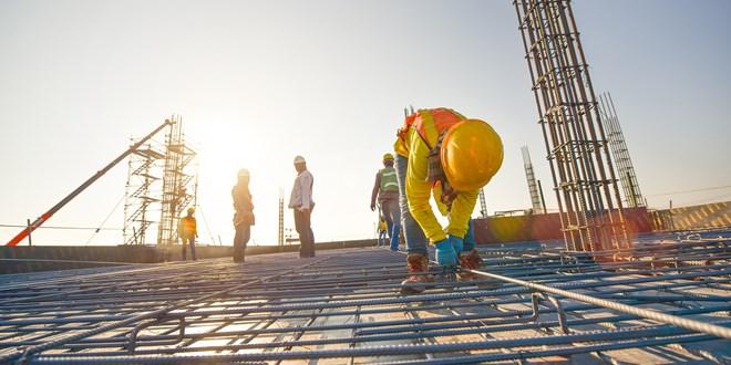 Inženirji pri delu zunaj na nedokončani betonski ploščadi, kjer se gradi novi objekt.